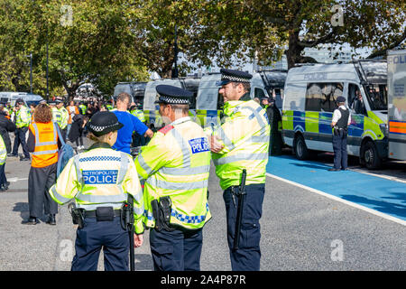 Millbank, London, UK 15th October 2019; Rear View of Three Police Officers at an Extinction Rebellion Protest With a Row of Police Vans in Background - Stock Photo