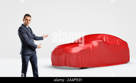 A businessman showing a car silhouette wrapped in a red cloth behind him. - Stock Photo