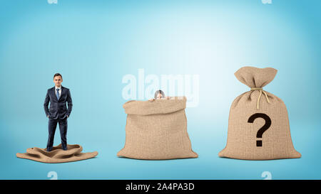 A businessman in an empty sack and a woman behind an open sack, and one sack closed with a question mark. - Stock Photo