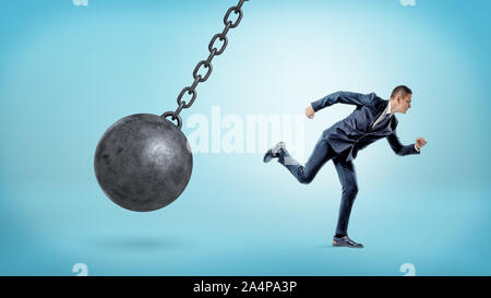 A small businessman running away from a giant black wrecking ball on a chain. - Stock Photo