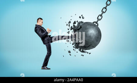 A businessman on blue background kicking at a wrecking ball and crashing it with many pieces flying away. - Stock Photo