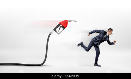 A businessman on white background running away from a red gas nozzle attached to a black hose. - Stock Photo