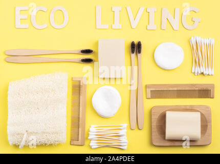 Eco living concept. Biodegradable bamboo toothbrushes, handmade packaging free soap and shampoo bars, cotton buds pads, luffa on yellow background, top view, selective focus - Stock Photo