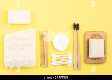Zero waste eco friendly concept. Bamboo toothbrushes, handmade packaging free soap and shampoo bars, cotton buds pads, luffa on yellow background, top view, selective focus - Stock Photo