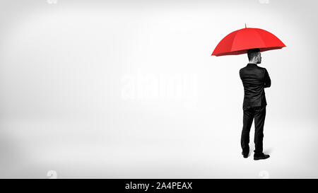 A high contrast view on a businessman standing in half-turn under an open red umbrella. - Stock Photo