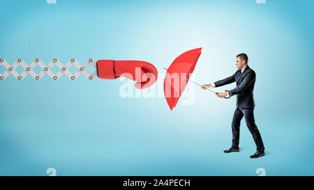 A small businessman holding a red umbrella to hide from a large boxing glove on a spring arm. - Stock Photo