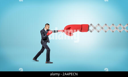 A small businessman in sport gloves punches a giant red boxing glove on a metal scissor arm. - Stock Photo