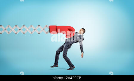 A businessman in side view gets hit with a large red boxing glove attached to a metal scissor arm on a blue background. - Stock Photo