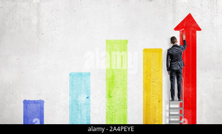 A businessman stands on a stepladder and draws with a paint roller several colorful chart columns. - Stock Photo