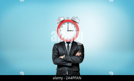 A businessman with crossed arms stands in a front view with a large red alarm clock instead of his head. - Stock Photo