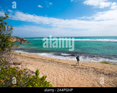 A woman walk on the beautiful deserted beach of Guanica Reserve in Puerto Rico.