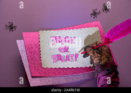 Creative purple and pink Halloween background with text 'Trick or treat', hand in black mesh glove holding glowing pink quill, with more paper cards a - Stock Photo