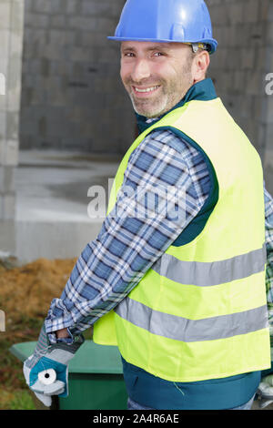 smiling building worker using a wheelbarrow - Stock Photo