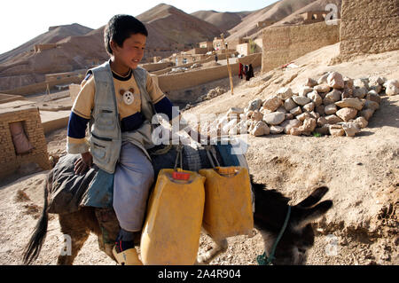 A boy transports water for his family on a donkey, in the village of Rag-e-shad, in central Bamyan province, Afghanistan. May 11, 2009. - Stock Photo