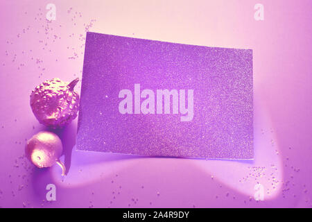 Creative purple Halloween background with two decorative pumpkins painted metallic pink and glittering paper card in spotlights with copy-space - Stock Photo