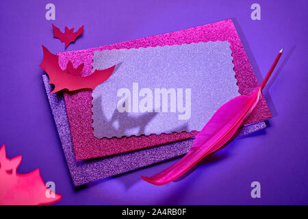 Creative Halloween background in glowing neon pink and purple with stack of glittering paper, quill and paper bats with long shadows. Copy-space on th - Stock Photo