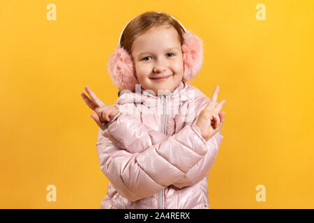 A cheerful little girl has crossed her arms and is showing a victory sign with her fingers. A child in a jacket and warm headphones on a yellow backgr - Stock Photo