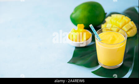 Yellow mango yogurt or smoothie on blue background with copy space left. Turmeric Lassie or lassi in glass. Banner - Stock Photo