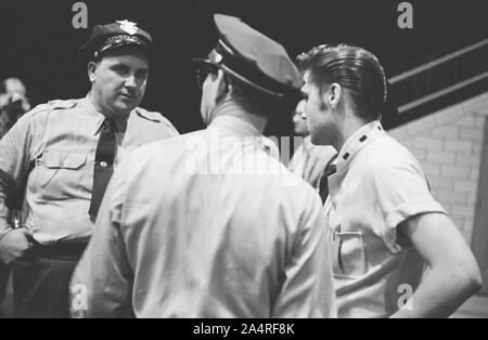 Elvis Presley speaks with police officers at the University of Dayton Fieldhouse, May 27, 1956. In the background at left is the photographer Marvin Israel.