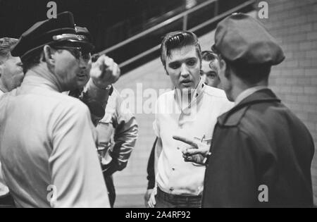 Elvis Presley speaks with police officers at the University of Dayton Fieldhouse, May 27, 1956. - Stock Photo