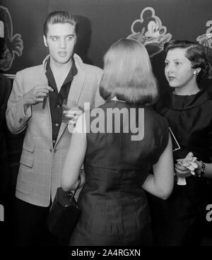 Elvis Presley speaking with fans at an adult party after his show at the Fox Theater, Detroit, Michigan, May 25, 1956. - Stock Photo