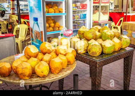 City stall selling ripe green and yellow coconuts close-up. - Stock Photo
