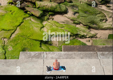 27.09.2019, Sydney, New South Wales, Australia - A man sunbathes on the shore of famous Bondi Beach and looks at rocks overgrown with algae. - Stock Photo