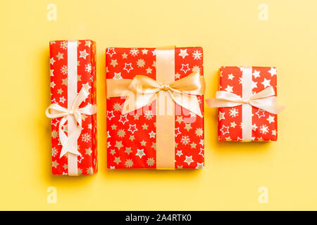 wrapped Christmas or other holiday handmade present in paper with gold ribbon on yellow background. Present box, decoration of gift on colored table, - Stock Photo