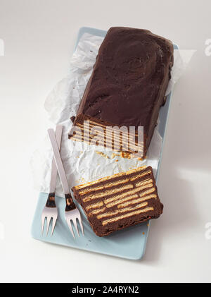 Top view of loaf-shaped chocolate cake with layers of biscuits. No bake traditional Kalter Hund sweet snack, served on ceramic blue tray on white tabl - Stock Photo