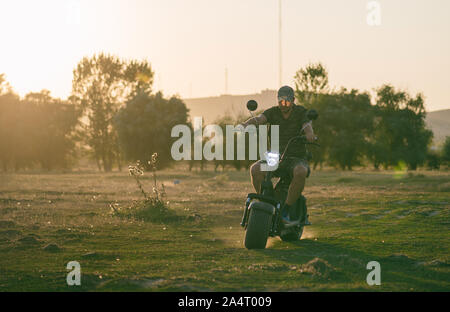 man on a motorized bicycle in sunset time - Stock Photo