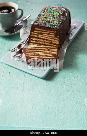 Loaf-shaped chocolate Kalter Hund no bake cake with topping, served on ceramic tray with cup of black coffee, viewed from high angle on cyan surface b - Stock Photo