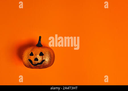 Halloween decoration concept - orange background with decorative pumpkin. Flat lay, top view. Place for your text. - Stock Photo
