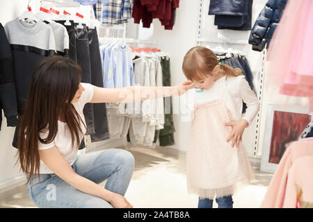 Young mother choosing new pink dress for little daughter in shop. Cheerful girl standing in store, trying on trendy outfit, and looking at clothes. Concept of shopping and buying. - Stock Photo