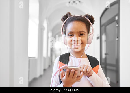 Pretty, positive schoolgirl with headphones holding phone, posing, looking at camera. Happy, beautiful child standing in long hallway, listening musik and smiling. - Stock Photo