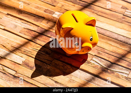 A yellow piggy bank stands on a wooden floor and casts a strong shadow - Stock Photo