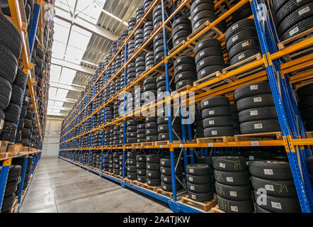 High rack with customer tires in warehouse of a tire dealer - Stock Photo
