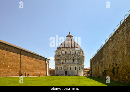 View of the Baptistery of St John in Piazza dei Miracoli with the exterior wall of the Monumental Cemetery and the town walls, Pisa, Tuscany, Italy