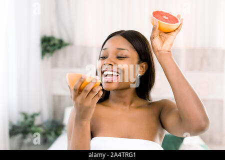 Photo of african american girl holding a half of grapefruit in front of her face and smiling on light background in spa. Skin care and beauty concept - Stock Photo