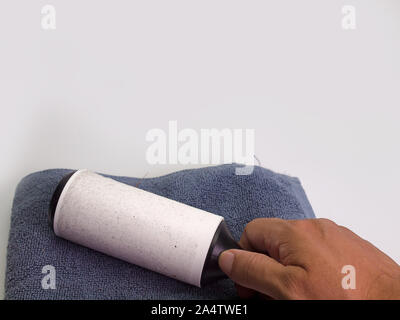 a man hand with  holding a white sticky brush for cleaning clothes - Stock Photo