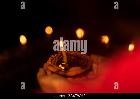 Indian woman or female holding diya or oil lamp in her hand during diwali celebration night. Background image for stock photo of Diwali. - Stock Photo