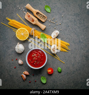 Italian food and menu concept. Spaghetti with ingredients sweet basil ,tomato ,garlic peppercorn and champignon on dark background flat lay and copy s - Stock Photo