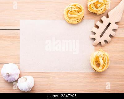 Italian foods concept and menu design . Blank paper and  pasta ladle on wooden background. - Stock Photo