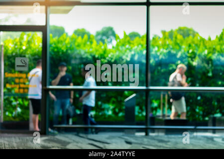 Blurred people smoking in smoking zone area of the mall or office. Four man smoke in smoking area beside green wall of tree. Quit smoke or smoking - Stock Photo