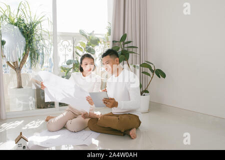 Happy asian couple planning their new apartment - Stock Photo