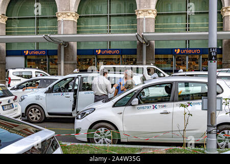 Turin taxi drivers talking whist waiting for a fare at the taxi rank  outside Porta Nuova railway station ,Turin,Italy - Stock Photo
