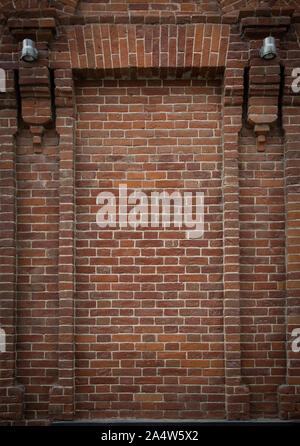 Brick alcove, niche with half-columns on each side and two lanterns. Abstract background with niche in old brick wall. - Stock Photo