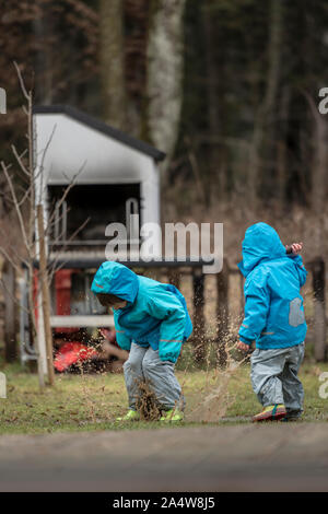 Two children wearing blue jackets playing outdoors in puddle. - Stock Photo