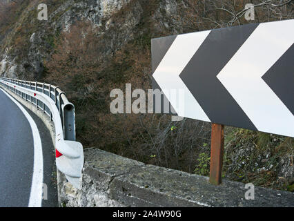 A left turn arrow sign ahead indicates a sharp turn in a mountain road - Stock Photo