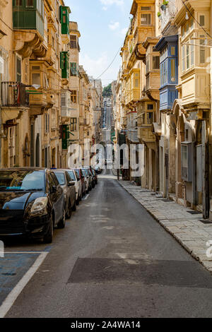 Typical Valletta street architecture with traditional Maltese wooden enclosed balconies and rising road, at Valletta, Malta - Stock Photo