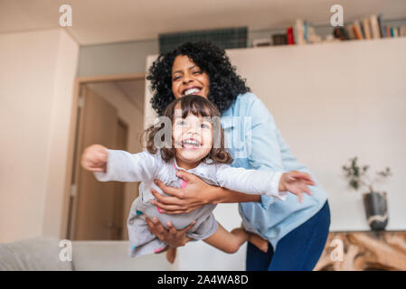Mother playfully swinging her little daughter in the air